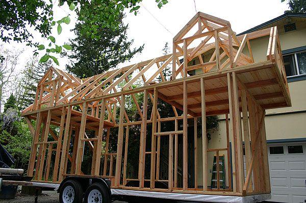 Pequeña vivienda de madera construida sobre un remolque de 24x8 pies, con dos espacios de altillo para dormir, con buhardillas. Cocina y cuarto de baño. Fotos.