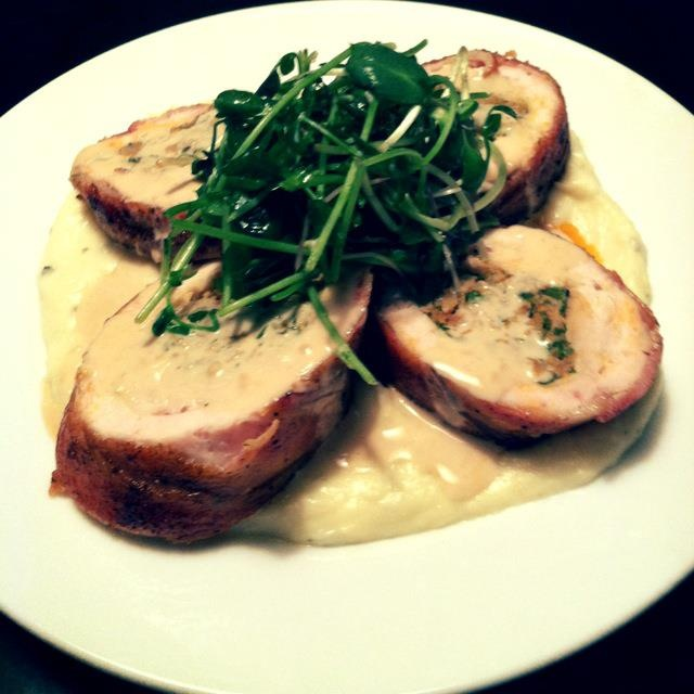 Bacon wrapped chicken sous vide stuffed with chorizo over parsnip puree topped with a microgreen salad