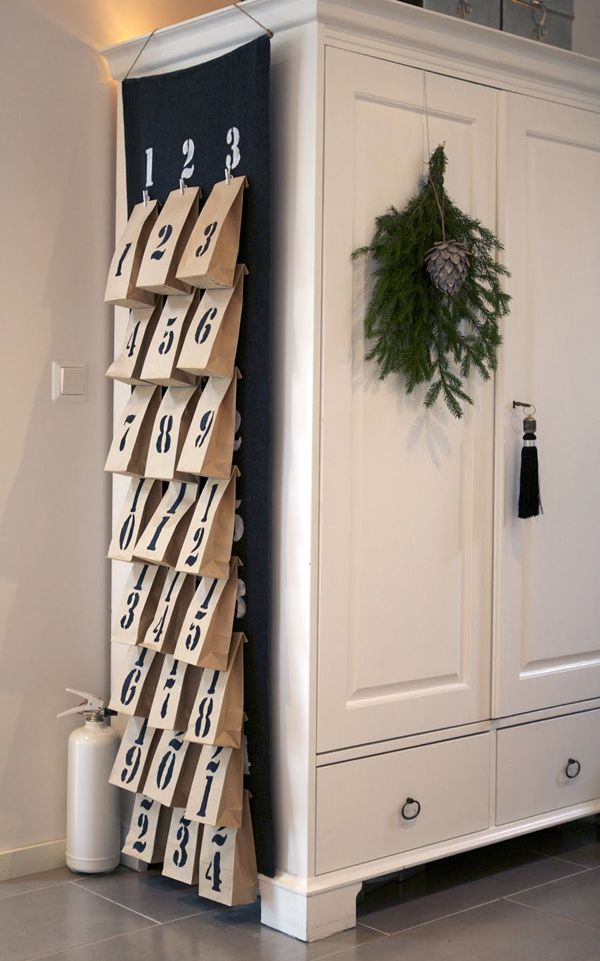Make an Advent Calendar: The calendar can be hung anywhere, on a piece of furniture or on a wall, both great assets when it comes to small-space holiday decorating. Here, small paper bags are clipped to a felt calendar. You can fill them with small holiday surprises such as chocolates, candies or other small finds.