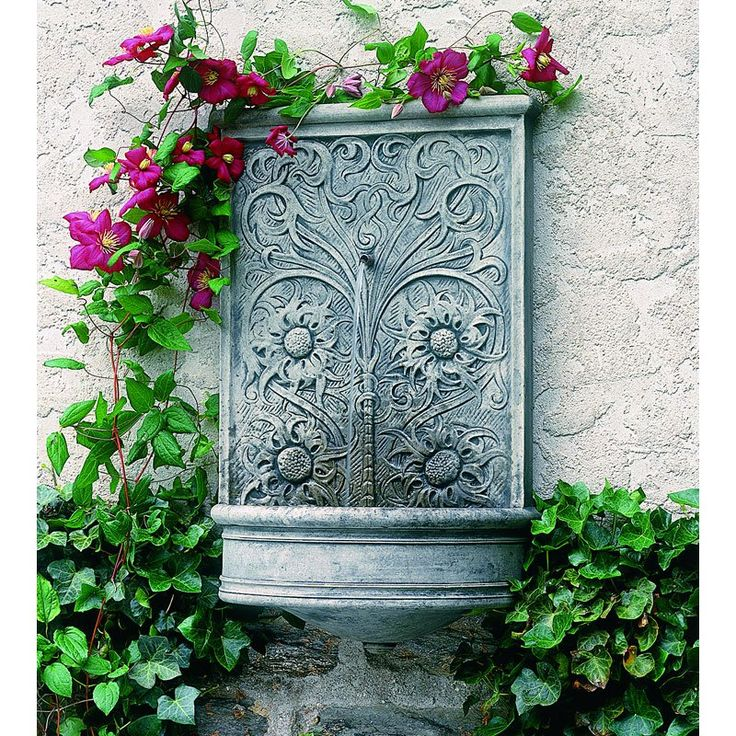 Another wall fountain with clematis growing around it.  Campania International Sussex Wall Fountain   www.simplyfountains.com
