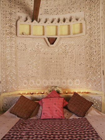Raised mud reliefs inlaid with mirror on the walls of bedroom in modern home in traditional tribal Rabari round mud hut, Bunga style, near Ahmedabad, Gujarat state, India, Asia