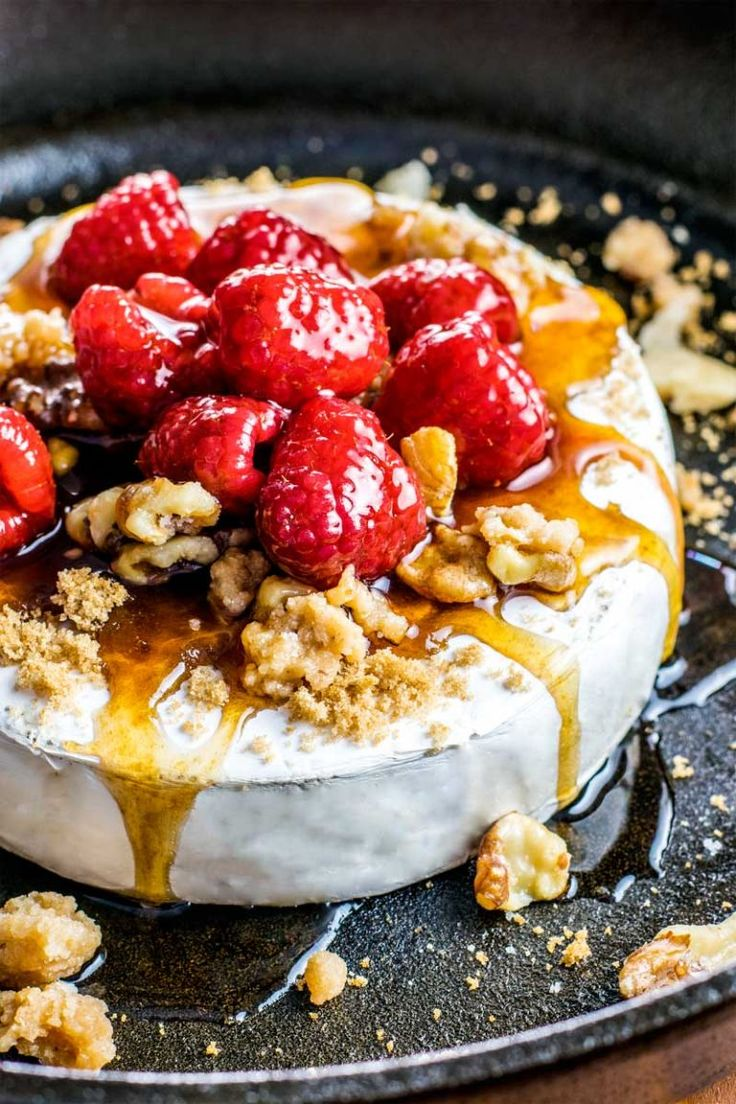 Raspberry and Walnut Baked Brie! An easy baked brie recipe that's topped with brown sugar, candied walnuts, and raspberries soaked in a honey balsamic sauce. | HomemadeHooplah.com