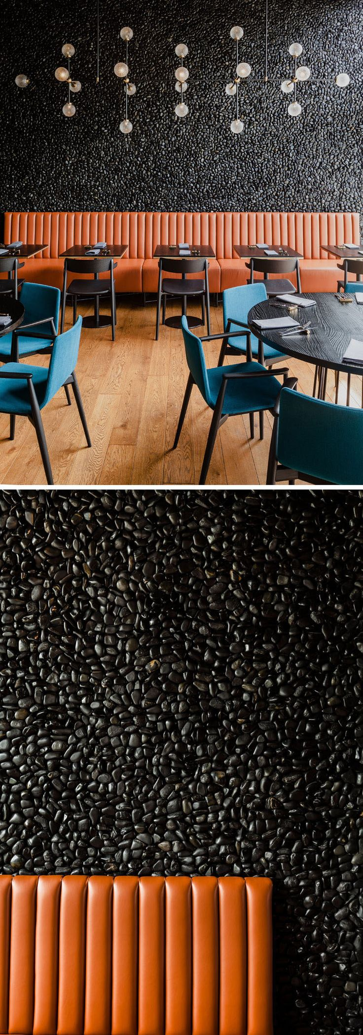Leather banquette seating sits against a background of hand-laid wall mosaic of black pebbles in this modern restaurant. #Pebbles #AccentWall #RestaurantDesign