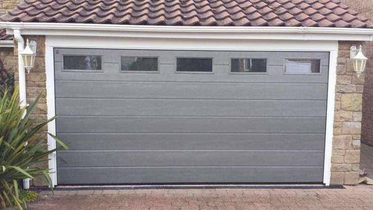 Hormann M Ribbed Sectional Garage Door By ABi Hormann M Ribbed insulated sectional garage door finished in RAL 9007 Grey Aluminium Wood Grain with glazing.