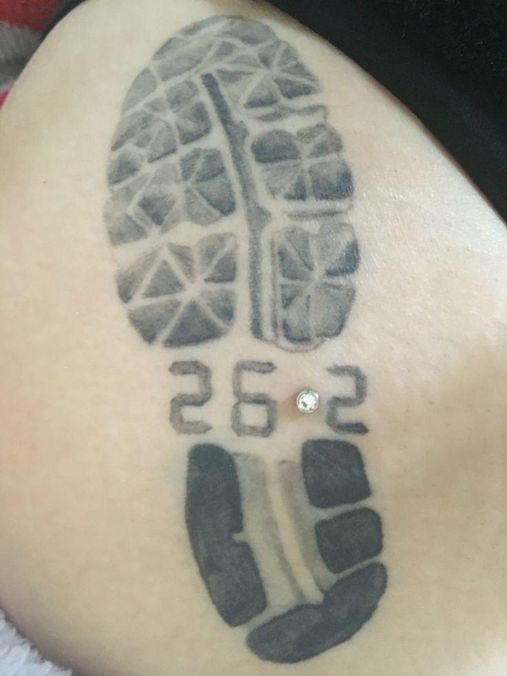 Marathon tattoo with dermal piercing on thigh and hip