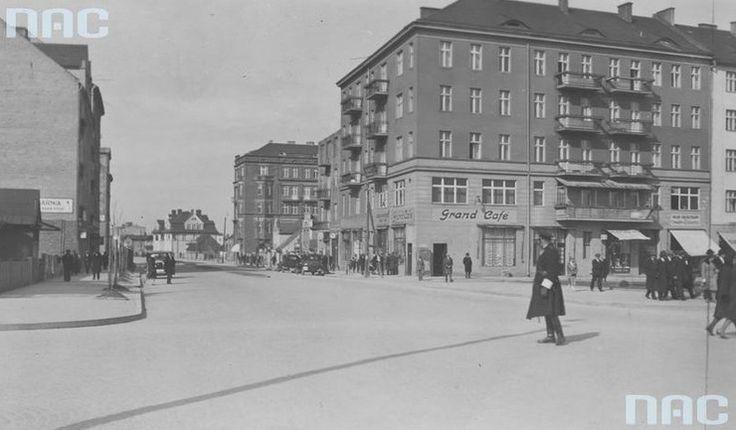 Policjant dyrygujący ruchem na ulicy Świętojańskiej. Widoczne samochody i kawiarnia Grand Cafe. Rok 1923 Na parterze znajdowała się kawiarnia Grand Café. W 1932 r. kamienicę wykupiła Komunalna Kasa Oszczędności, która w 1937 r. dokonała gruntownej przebudowy budynku, podwyższając go o jedną kondygnację, likwidując spadzisty dach oraz balkony. W ten sposób budynek stał się przykładem odmiany modernizmu zwanej funkcjonalizmem.