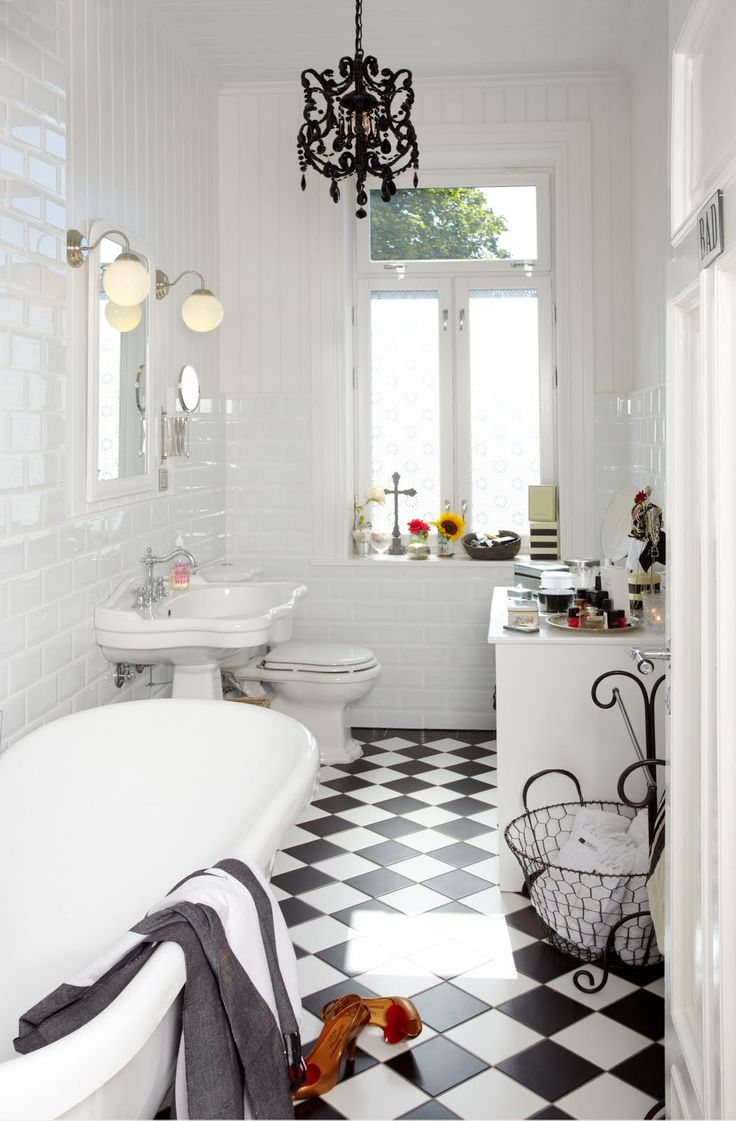 classic b/w flooring with touches of filigree in accessories and light fitting are the key pieces to this lovely white bathroom.