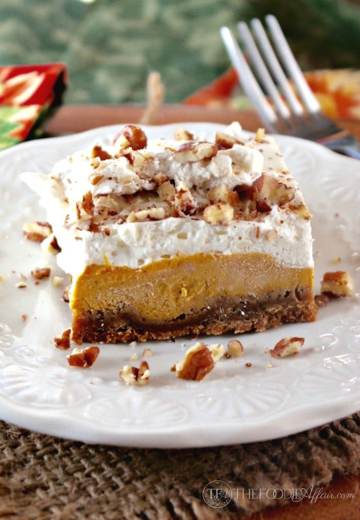 Light and airy pumpkin delight dessert is three layers of delicious Fall flavors: gingersnap crust, creamy pumpkin filling with cream cheese, and fresh whipped cream all topped with chopped pecans!