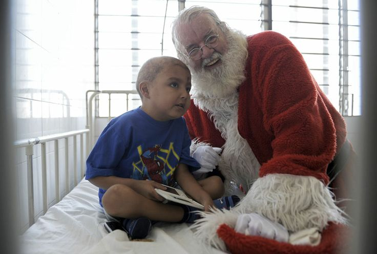 Icelandic philanthropist Einar Sveinsson, dressed as Santa Claus, speaks with a patient at the oncology ward during a visit to the Benjamin Bloom National Children Hospital, in San Salvador, on December 11, 2012. Sveinsson has visited the hospital prior to Christmas every year since 2001 to give gifts to the patients