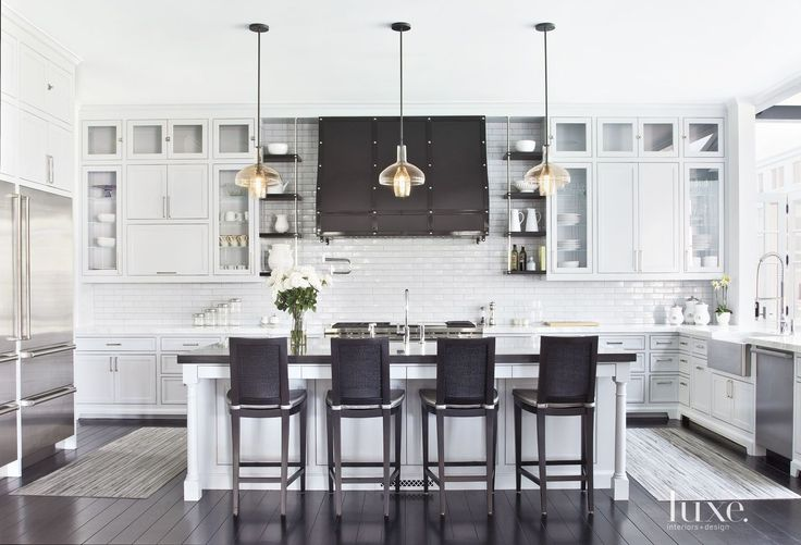 A trio of pendant lights by Alison Berger for Holly Hunt illuminates the kitchen cabinetry's dove gray hue. Hunter and Giannetti designed the custom hood, and Hunter upholstered bar chairs from David Sutherland with a textile by Innovations.