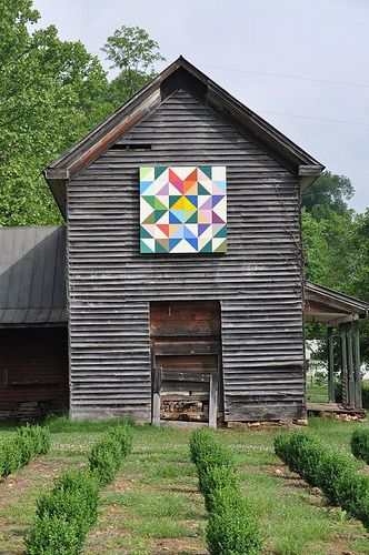 This no long occupied house sits beside a nursery stock of boxwoods. What appears to be an old door is actually the location of a dismantled chimney. The owners added a colorful quild square block.