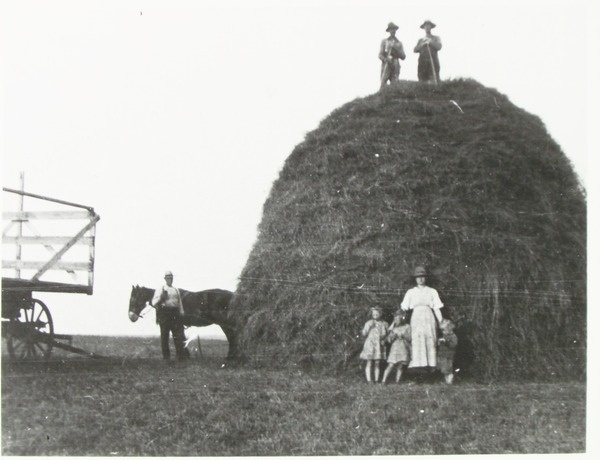 If you're scared of heights, don't climb on this stack of hay! Men at Top of Hay Stack | saskhistoryonline.ca