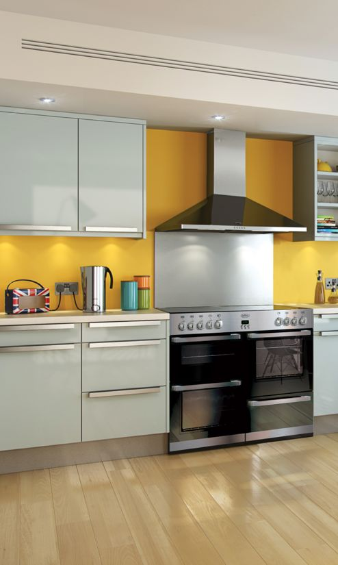 Belling make all their range cookers in Great Britain. This models has lots of black glass and modern stainless steel trims. Paired here with a chimney hood and splashback | Roberts Radio Union Jack DAB digital radio | Inspirational kitchen | Wooden floor | Yellow wall