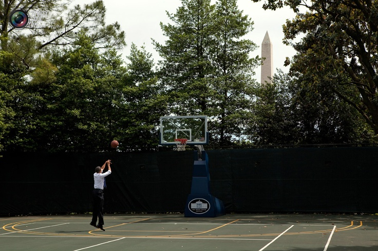 U.S. President Barack Obama shoots hoops on the White House Basketball Court in White House handout photograph.