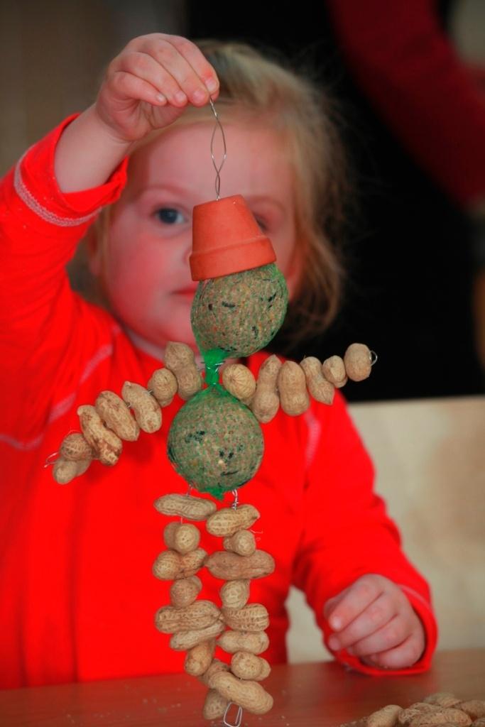 Poppetjes van vogelvoer. Het lijfje van vetbollen, armen en benen van pinda's gereigd met staaldraad. Een klein potje is het hoedje.