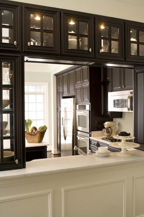Elegant kitchen with espresso see through glass cabinets over white marble topped pass through. The ceiling height espresso cabinets pair with polished nickel hardware alongside white marble countertops. The cabinets frame a stainless steel counter-depth refrigerator beside the stainless steel double oven and above the range microwave. The pale gray walls pair with simple white trim over rich hardwood floors.