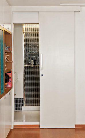 """Compacto, porém com direito a boxe e chuveiro, o novo ambiente abre-se para o estar. Ocupa a área voltada para a cozinha e parte do antigo dormitório de empregada. Uma porta de correr fecha o cômodo. """"Ela não só economiza espaço como também é uma solução bastante elegante"""", afirma a arquiteta Joanna Fraga. Misturadas às pastilhas pretas do rodapé alto e do interior do boxe, estão a pintura e o piso brancos. Revestimento da parede da Atlas (pastilhas de porcelanas pretas, com 1,5 x 3 cm…"""