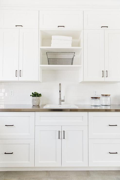 Beautiful laundry room features white shaker cabinets adorned with oil rubbed bronze hardware paired with stainless steel countertops and a white subway tiled backsplash.