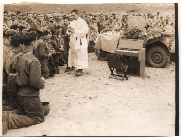 Memorial Service on Beach-Head for Those Who Fell in the Assault. With the bonnet of a Jeep as an Altar a U.S. Army Chaplain conducted a Memorial Service for those who fell at the first U.S. cemetery to be laid out on a French beach-head. Troops kneel in prayer as the Chaplain celebrates Communion…14/6/44