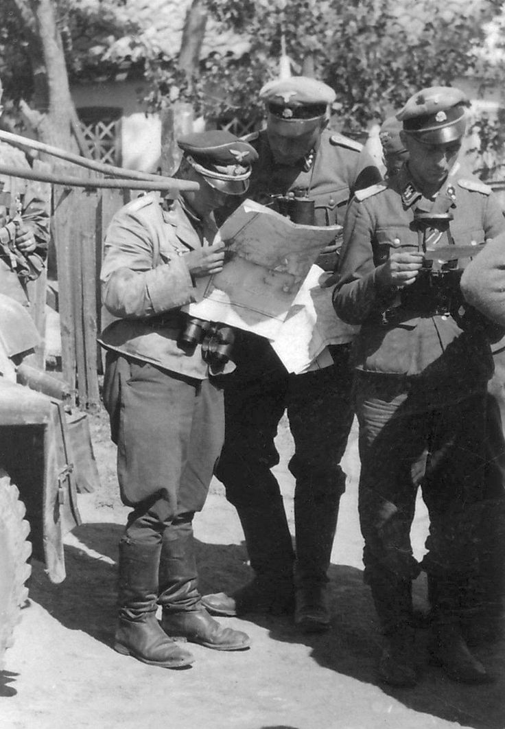 July 1941: SS-Kriegsberichter Paul Augustin photographed Knittel (in the middle) while he studied a map with one of the liaison officers from the Luftwaffe. To their right SS-Untersturmführer Erich Grätz. To their left a four-wheeled Sd.Kfz. 223 armoured communications vehicle.