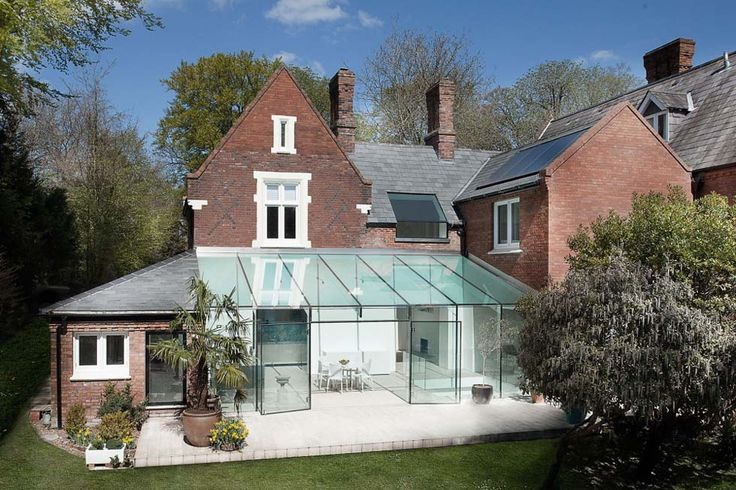 A frameless galss extension on a Victorian house * perhaps add glass exterior to transform parking space into indoor/outdoor garden