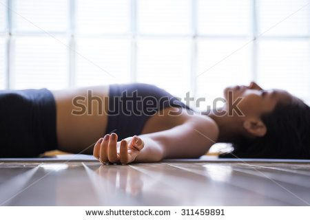 Young woman practicing in a yoga studio. Shavasana or corps pose is the end of a class or practice. - stock photo