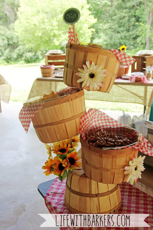 A co-ed rustic country backyard park bbq barbeque themed baby shower. Orchard basket snack tower. Pretzels and chips in baskets.