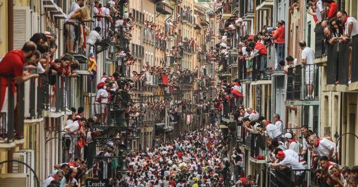 """20160710 - Milhares de pessoas participam do quarto dia dos """"encierros"""", corridas atrás de touros, em Pamplona, na Espanha, parte da celebração de São Firmino. Durante o festival, touros são soltos por ruas estreitas, onde perseguem os corredores, que usam lenços vermelhos e atiçam os animais. Um espanhol morreu e dois outros homens, incluindo um japonês, ficaram feridos nas realizadas na cidade neste sábado (9) Imagem: Pedro Armestre/AFP"""