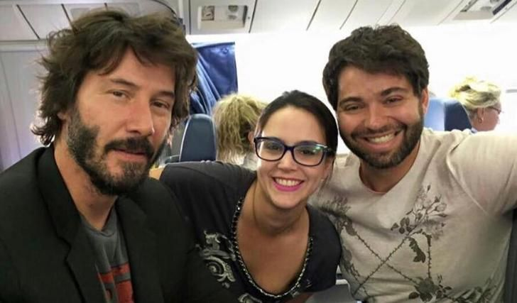 Keanu Reeves smiling in this picture after he paid for excess baggage charges for a couple who did not have enough money.