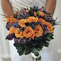 Hand-tied bridal bouquet of orange roses, black ti leaves, blue thistle, bird of paradise and tropical greens.