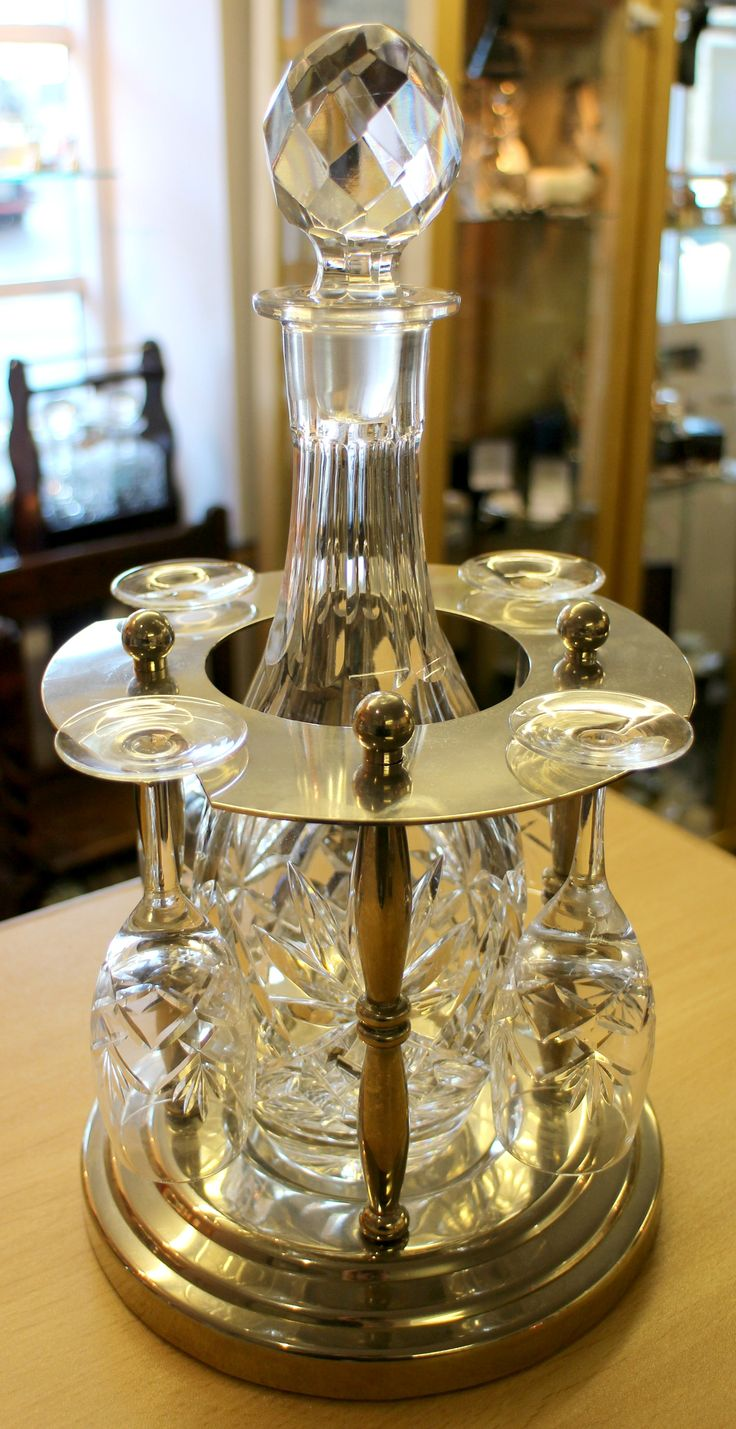 Liqueur set with a plated stand. Set includes a tall cut glass decanter and four glasses. Excellent condition, no damage. Overall height measures approximately 14.5 inches. Diameter of stand measures 7 inches.