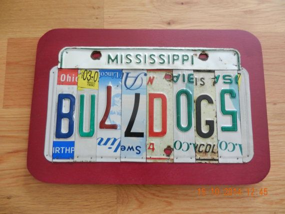 This unique item is a Mississippi State Bulldogs license plate sign that reads Mississippi Bulldogs is made from vintage license plates and