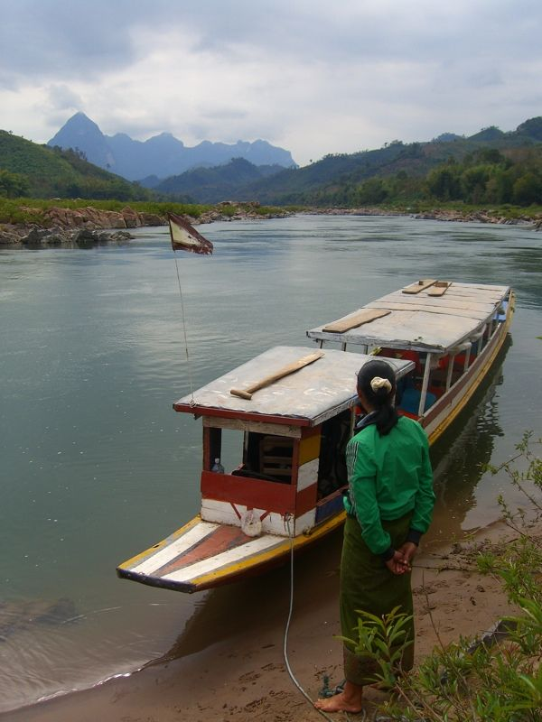 A boat trip along the Mekong River from Luang Prabang to Nong Khiaw (Nong Kiau) in Laos features limestone cliffs, water buffaloes and scores of waving kids.