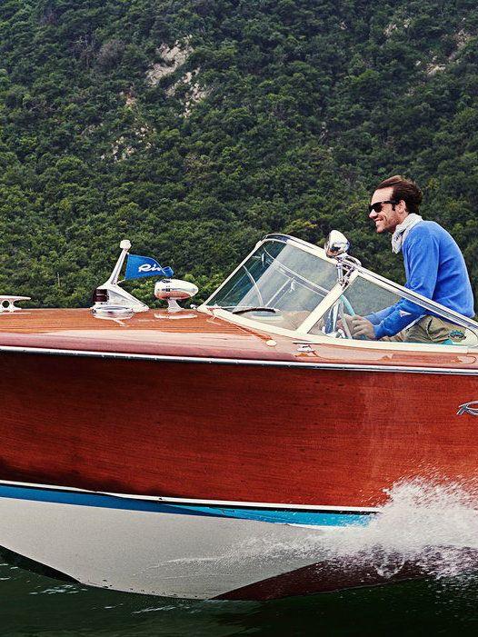 A vintage Riva boat speeding towards Monte Isola on Lake Iseo.