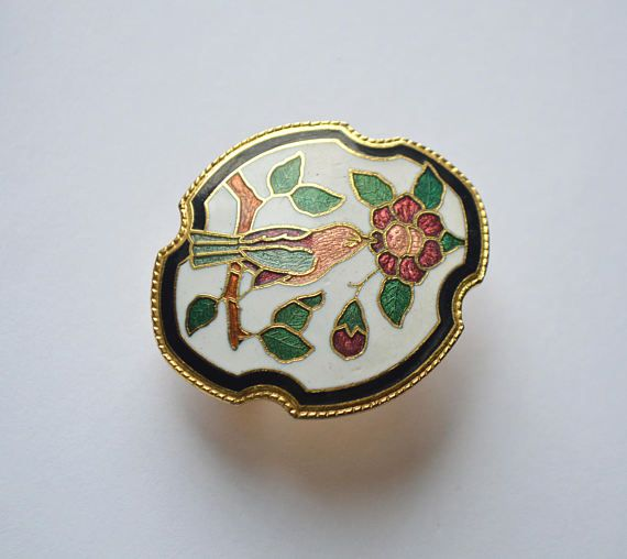 A beautiful spring-blooming vintage floral scarf ring/clip. It is gold framed with white enamel background cloisonne design. It features a bird sitting on a branch being attracted by the blooming flowers nectar. All in reddish-orange-greenish tone with a golden rim made in cloisonne style.  Cloisonne (from french Cloisonné) is an ancient enamel process for decorating metalwork objects. It improved during the late nineteenth and twentieth centuries and cloisonné decorative items, jewelle...