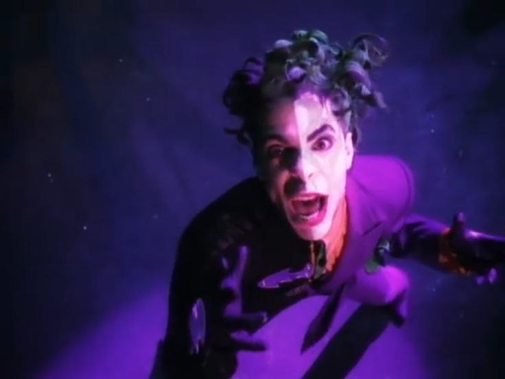 """The music video to Prince's BATDANCE (1989). I was in love with it. The song is a strange mishmash of dialogue, riffs, grooves, snippets of unreleased songs, and sound effects, enlivened by a purple-hued ballet duel between multiple Jokers and Batmen—and Vicky Vales, walking onto the set straight from what seems to be an assembly line. In the middle of all that there's Prince, or """"Gemini"""", one part Batman, one part Joker."""