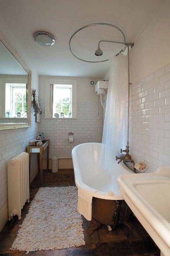 Roll top bath with white metro tiles and shower