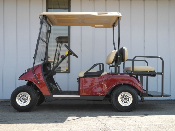 This custom deep red 2007 E-Z-GO gas golf cart is street-ready and loaded with features including a brand new CGS body, custom deep red paint, rear flip seat, premium lights, standard hard top, 4-panel rear view mirror, windshield, and more.