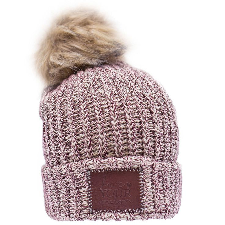 This pom beanie is knit out of 100% cotton yarn in natural and burgundy colors. It features a brown leather patch that is debossed with the Love Your Melon logo and a detachable, natural faux fur pom.