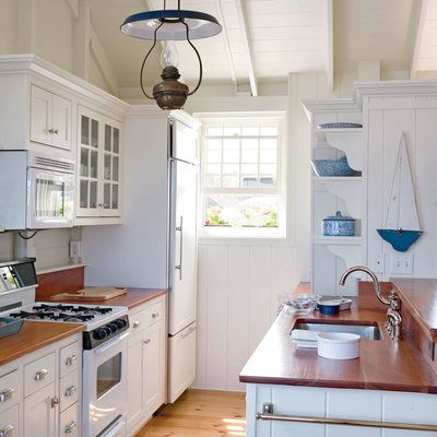 A nautical kitchen with white cabinets, mahogany countertops, and brushed-nickel hardware.
