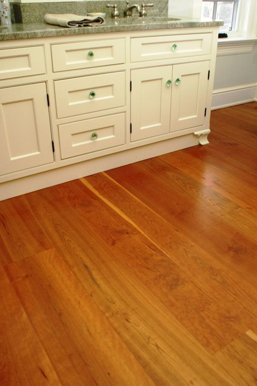 love the warm hue of these cherry wood floors and the green tinted knobs on the