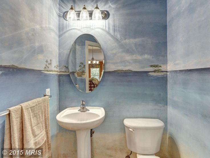 Tropical Powder Room With Howard Elliott Oval Mirror Moen