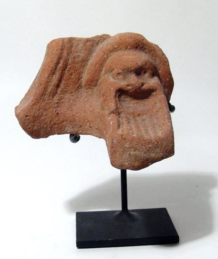 Egyptian terracotta head of Silenus, 3rd-1st century B.C. Ptolemaic Period, Greek terracotta pot support with mask of Papposeilenos with long striated beard, within an arched panel, the back is plain, the edge of the fire bowl still evident, 11.6 cm high. Private collection