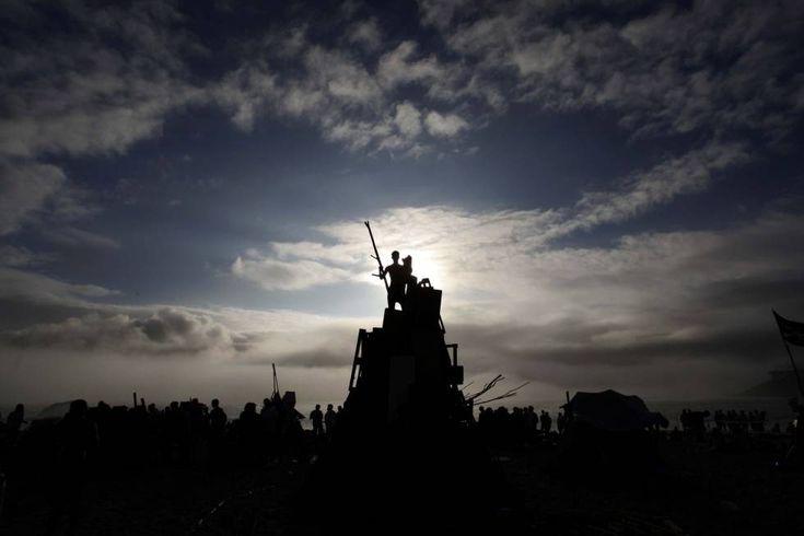 Un joven sobre uno de los montones de madera que arderán a medianoche hoy en A Coruña donde se disfruta un año más la tradicional festividad de San Juan.