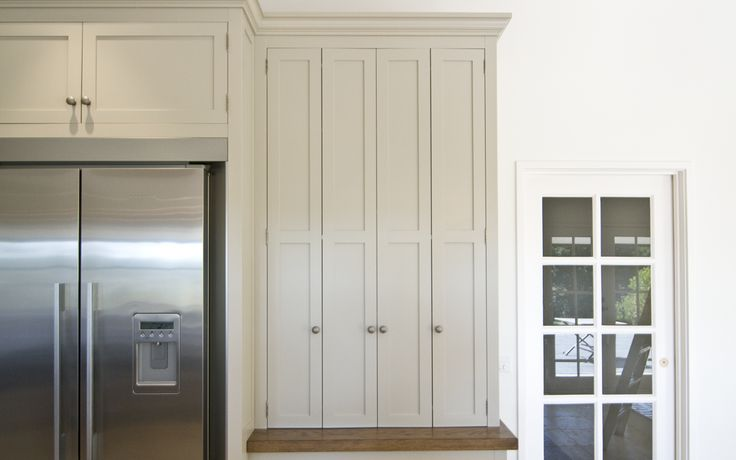 Hampton style kitchen includes a handy concealed appliance cupboard with bi fold doors.