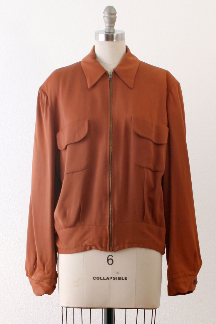 An incredibly handsome gabardine jacket in a deep rust-color. A whimsical satin with a motif of fishing poles; fishing nets; fish, etc. Brass Conmar locking zipper front closure. Rounded collars and c