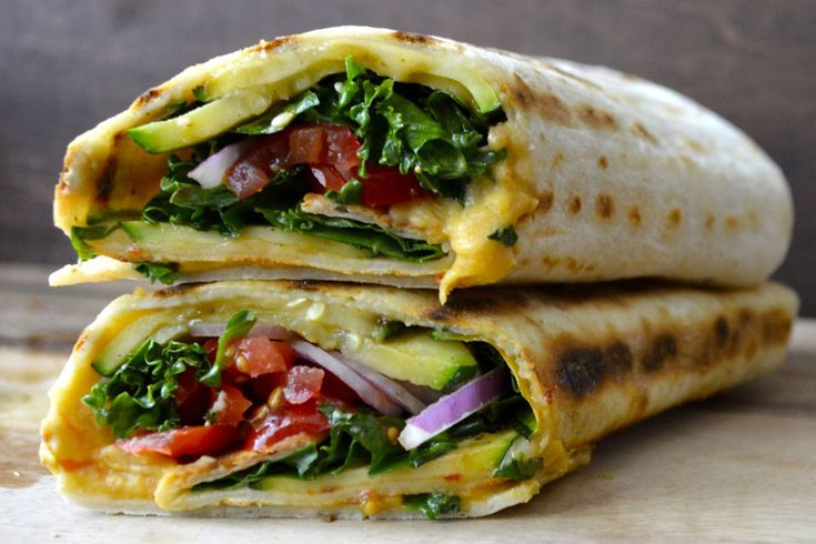 This wrap from Maebells is packed with grilled zucchini, veggies, cheese and hummus! Grilled zucchini is placed on a nice big tortilla topped with kale, red onion, tomatoes, cheese, and a heaping d...