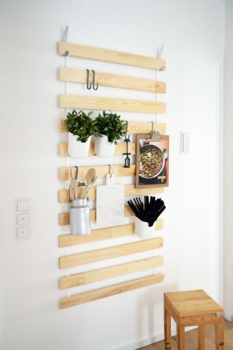 REPURPOSE BED SLATS AS A WALL HANGER – This $10 IKEA hack really thinks outside the bed box. The SULTAN LADE usually hides under the mattress, but the wooden planks can hold magazines, kitchen herbs and even shoes when hung vertically. Click through for the full tutorial and for more storage solutions.