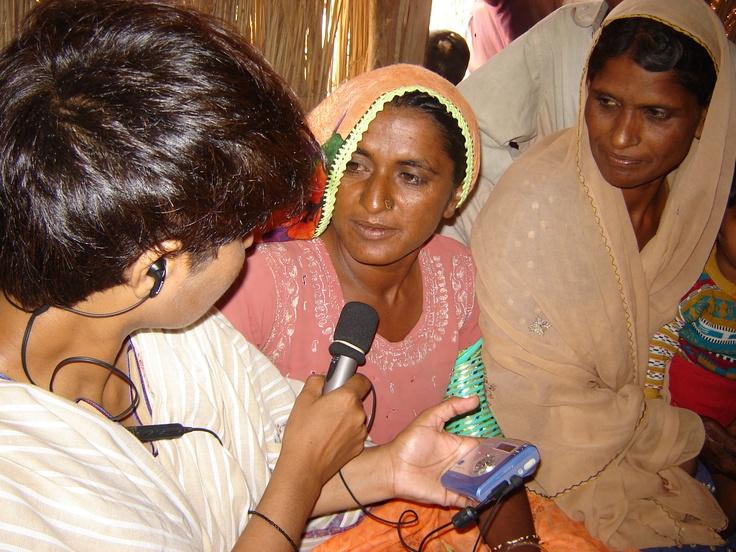 A journalist interviews two women in Pakistan.
