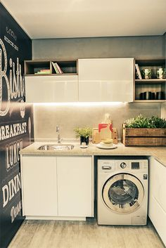 Lavanderia com parede adesivada. Iluminação nos armários é um charme a parte! Ótima opção para espaços compactos